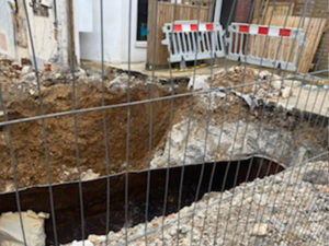 Large hole excavation demolition project protected by barriers