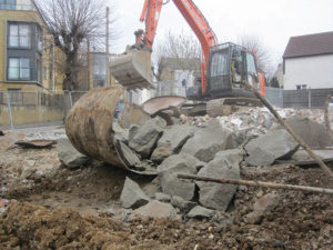 Excavator removing large rubble from demolition site